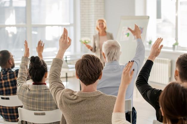Achter mening van verscheidene slimme studenten die hun handen opheffen bij les om vraag van hun leraar te beantwoorden