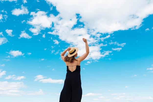 Achter mening van vrouw die van de in openlucht vrijheid met hemel en wolken genieten