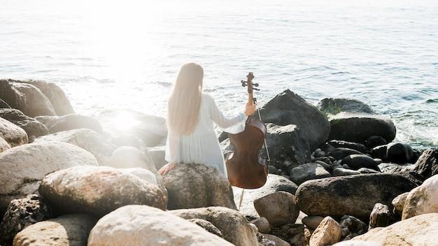 Achter mening van vrouw met cello door de oceaan