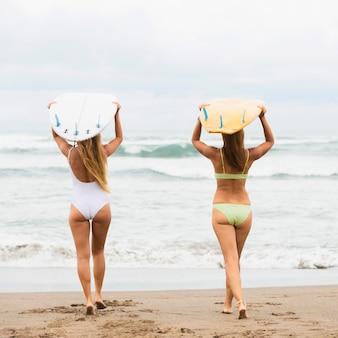 Achter mening van vrouwen die surfplanken dragen bij het strand