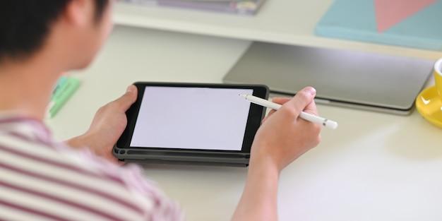Achter schot van jonge creatieve man puttend uit witte leeg scherm computertablet door stylus pen.