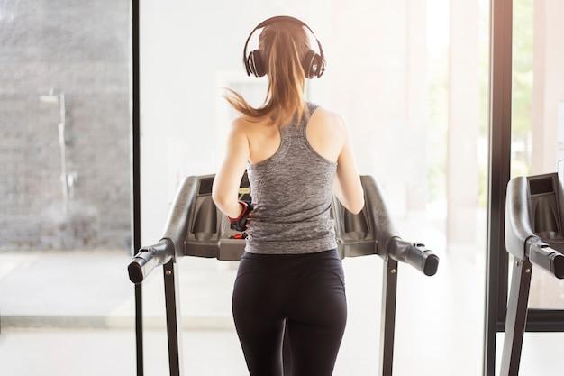 Achter sportvrouw die op tredmolen in gymnastiek, gezonde levensstijl aanstoten