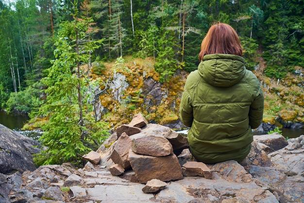 Achter van jonge vrouw bewondert de noordelijke natuur. persoon zittend op de rotsen