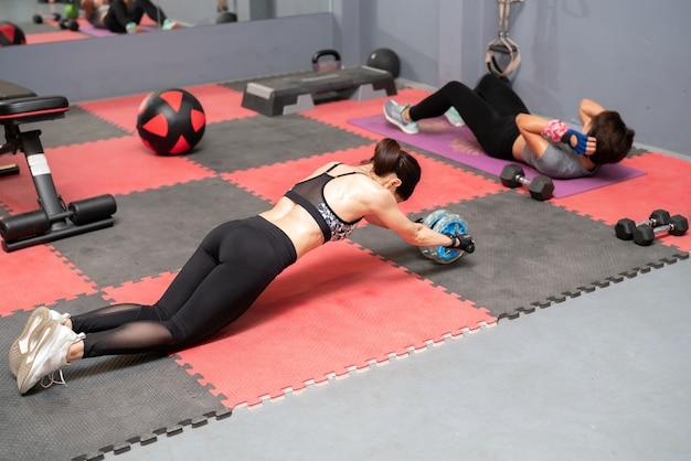 Achter zijaanzicht van een jonge vrouw in sportkleding training met ab wiel op gym achtergrond.
