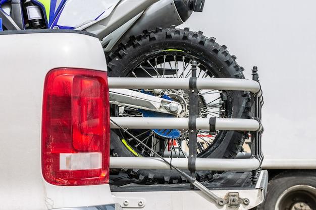 Achteraan met twee crossmotoren op de achterkant van de truck met veiligheidsuitrusting in woonomgeving.