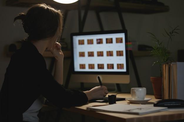 Achteraanzicht afbeelding van geconcentreerde jonge dame ontwerper
