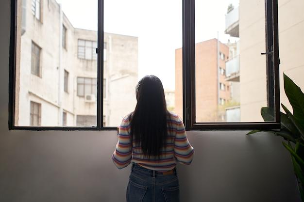 Achteraanzicht afrikaans meisje dat uit het raam leunt en naar buiten kijkt waar grote gebouwen zijn