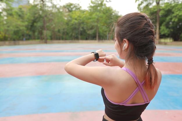 Achteraanzicht atletische jonge gezonde aziatische vrouw in sportkleding die staat en fitnesstracker gebruikt op slimme horloge na het uitrekken buiten voor ochtendoefening. sport- en technologieconcept