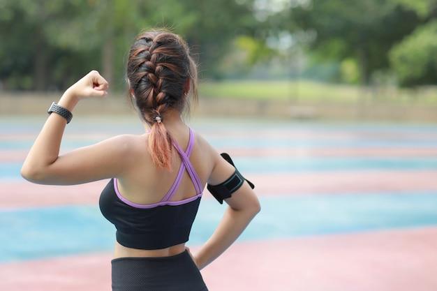 Achteraanzicht atletische jonge gezonde aziatische vrouw in sportkleding die staat en hand buiten opsteekt voor ochtendoefening. actief meisje trainen op biceps stretching oefening. sport en lifestyle concept