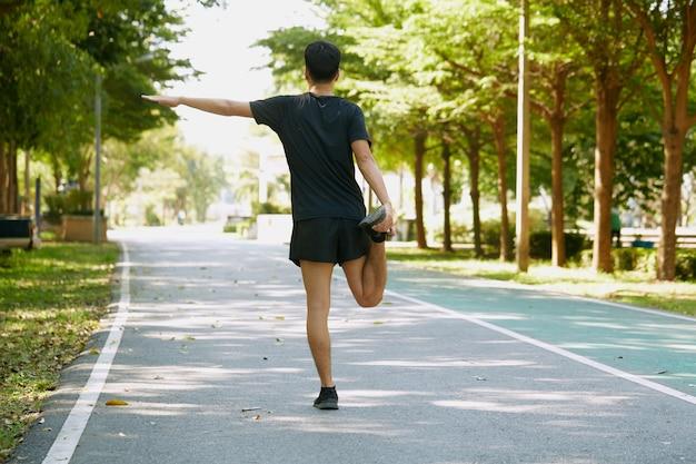 Achteraanzicht aziatische knappe mannen opwarmen voordat ze 's ochtends in het park wandelen en joggen.