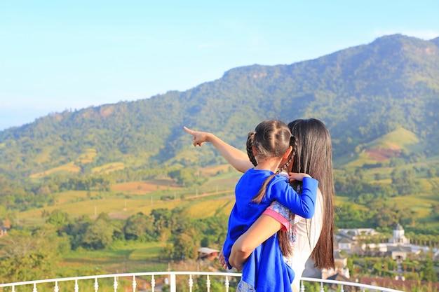 Achteraanzicht aziatische moeder die dochter op balkon op de heuvel en wijst erop dat te zien.