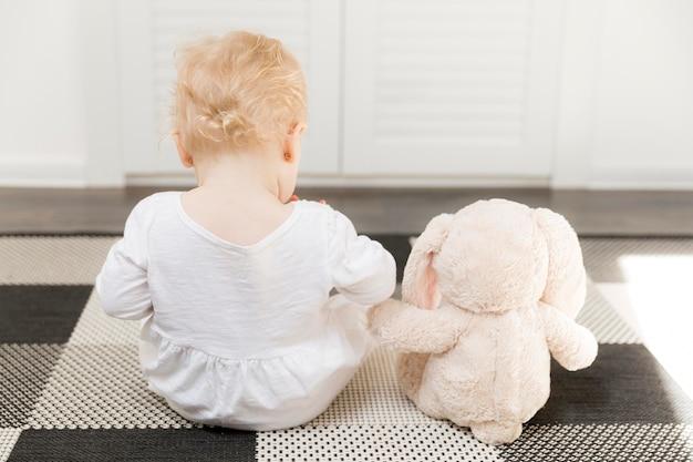 Achteraanzicht babymeisje met speelgoed
