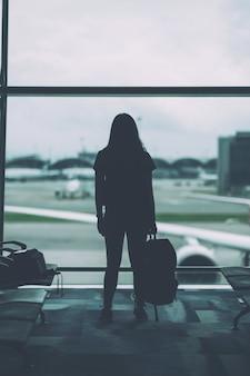 Achteraanzicht beeld van een vrouwelijke reiziger met rugzak op de luchthaven