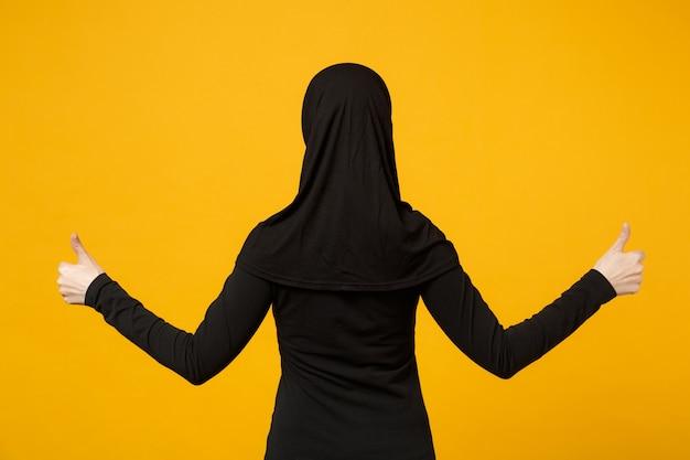 Achteraanzicht beeld van jonge arabische moslimvrouw in hijab zwarte kleding met duimen omhoog geïsoleerd op gele muur, portret. mensen religieuze levensstijl concept.