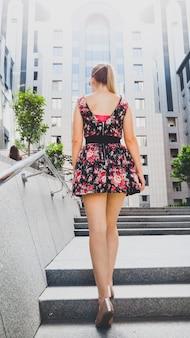 Achteraanzicht beeld van mooie jonge vrouw met lange benen in korte jurk die de stenen trap oploopt op straat in de stad