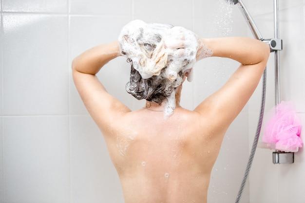 Achteraanzicht beeld van mooie sexy vrouw wassen hoofd