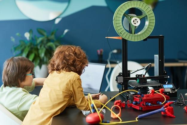 Achteraanzicht bij twee jongens die een robot bouwen en een 3d-printer gebruiken tijdens de techniekles op school, kopieer ruimte