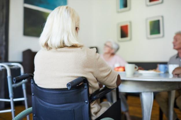 Achteraanzicht bij witharige oudere vrouw die in een rolstoel zit in de kopieerruimte van het verpleeghuis