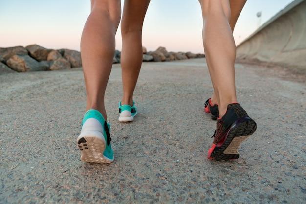 Achteraanzicht bijgesneden afbeelding van twee jonge vrouwen in sneakers