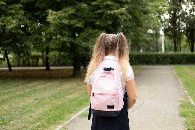 Achteraanzicht blond krullend schoolmeisje in schooluniform met roze rugzak terug naar school buiten
