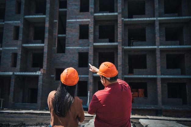 Achteraanzicht bouwers een man en een vrouw in oranje helmen staan bij een bakstenen flatgebouw in aanbouw. voormannen volgen de voortgang van de bouw van het object.