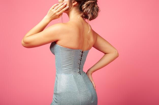 Achteraanzicht close-up op de achterkant van jonge vrouw in blauwe glanzende strakke jurk met vetersluiting op roze geïsoleerde rug...