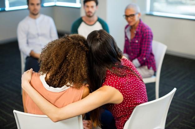 Achteraanzicht creatieve zakenvrouw elkaar omhelzen op kantoor