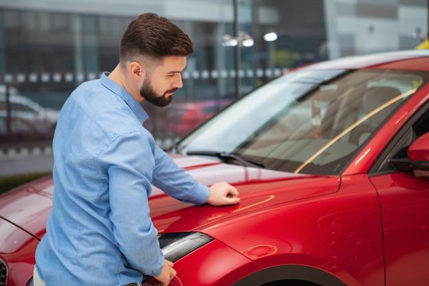 Achteraanzicht dat van een mannelijke klant is ontsproten die rode auto bij autodealer onderzoekt, exemplaarruimte