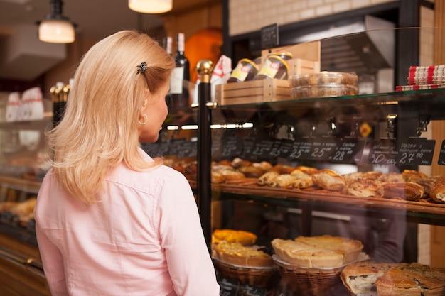 Achteraanzicht dat van een vrouw is ontsproten die gebak uit bakkerijvertoning kiest