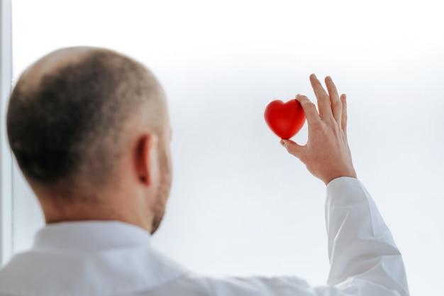 Achteraanzicht. dokter kijkt naar het kleine rode hart in zijn handen. het concept van gezondheidsbescherming.