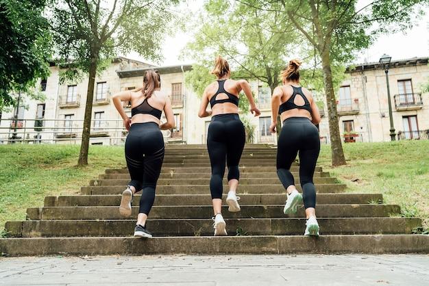 Achteraanzicht drie mooie vrouwen rennen de trap op van een park met veel stadsbomen, alle drie gekleed in zwarte sportkleding