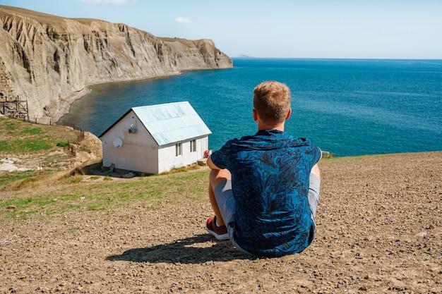 Achteraanzicht een jonge man voor een wit eenzaam huis aan de rand van een klif