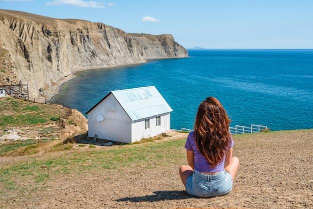 Achteraanzicht een jonge vrouw voor een wit eenzaam huis aan de rand van een klif