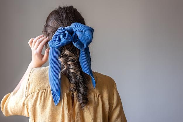 Achteraanzicht een meisje in een jurk met een strik in het haar op een grijze achtergrond