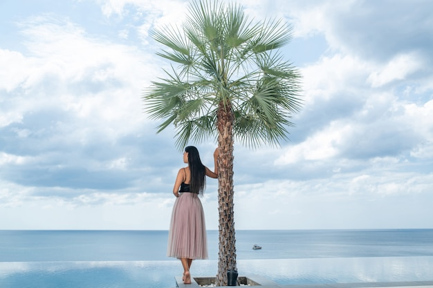 Achteraanzicht: een mooie langharige vrouw in een zomerjurk staat bij een palmboom en een overloopzwembad en bewondert het uitzicht op zee
