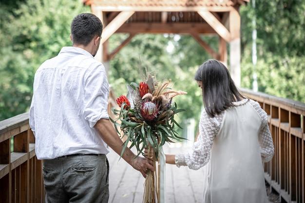 Achteraanzicht, een verliefd stel met een boeket met exotische proteabloemen.
