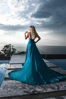 Achteraanzicht: elegante blonde poseren in een lange avond blauwe jurk in de buurt van het zwembad. luxe ontspanning. zeezicht.