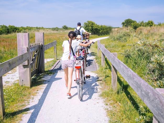 Achteraanzicht fietsers familie reizen op de weg in het duingebied van het eiland schiermonnikoog.