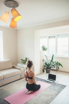 Achteraanzicht foto van een blanke vrouw zittend op de vloer in sportkleding en kijken naar het scherm van de laptop