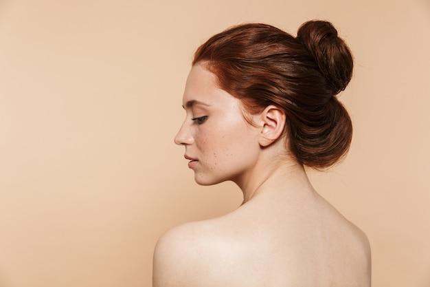 Achteraanzicht foto van een jonge roodharige vrouw geïsoleerd poseren.