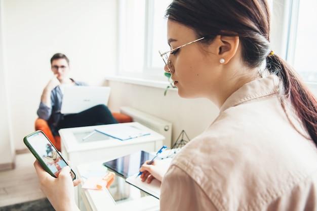 Achteraanzicht foto van een jonge zakenvrouw chatten op de telefoon tijdens het werken aan het bureau met haar man