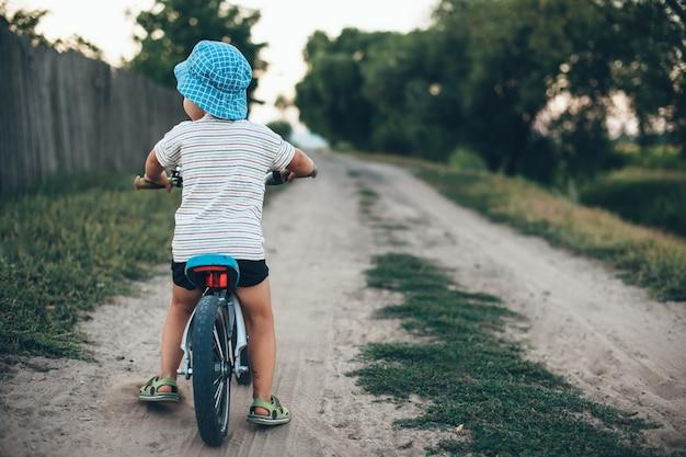 Achteraanzicht foto van een jongen op een fiets met een hoed en lopen op een landweg