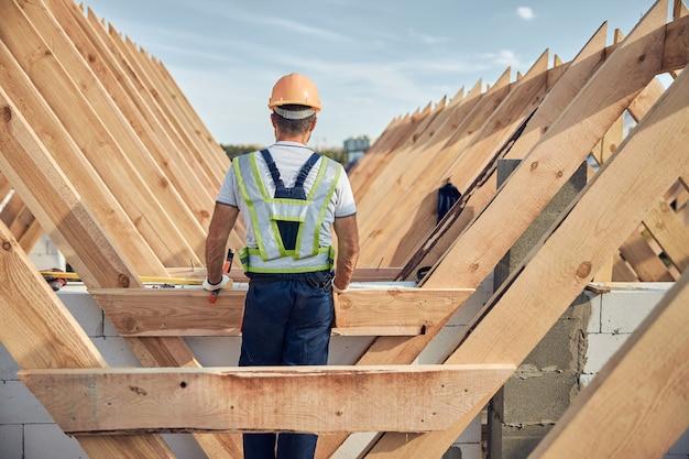 Achteraanzicht foto van een man met een veiligheidshelm en een goed zichtbaar vest die bij een houten dakframe staat