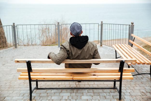 Achteraanzicht foto van jonge afrikaanse man op een bankje