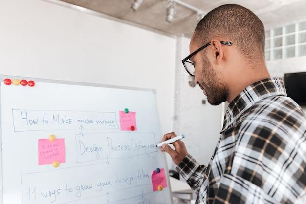 Achteraanzicht foto van jonge afrikaanse zakenman met een bril in kantoor werken met flip-over.
