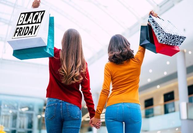 Achteraanzicht foto van twee jonge vrouwen in kleurrijke kleding met boodschappentassen in handen met print erop van zwarte vrijdag.