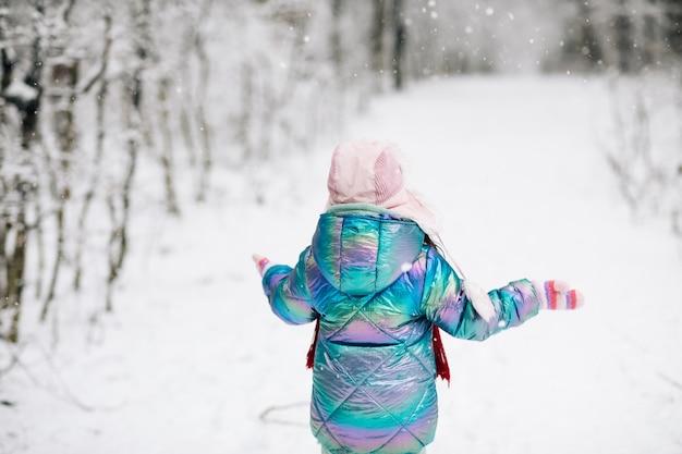 Achteraanzicht gelukkig lachend kind, schattig meisje in een kleurrijke kleding en hoed Premium Foto