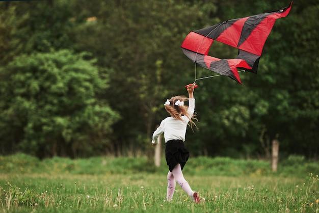 Achteraanzicht. gelukkig meisje in vrijetijdskleding met vlieger in het veld. prachtige natuur