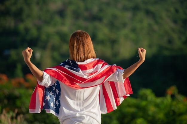 Achteraanzicht gelukkige jonge vrouw poseren met de nationale vlag van de vs die buiten staat bij zonsondergang.