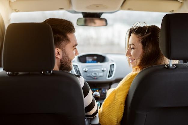 Achteraanzicht in een auto van mooie jonge gelukkige liefde paar op zoek naar elkaar.